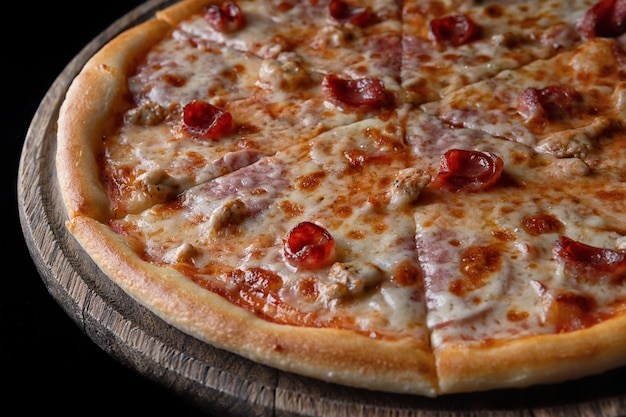 나무 판에 피자, 고기, 소시지, 닭고기, 검정색 배경에 4 고기
