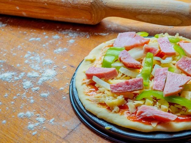 밀가루를 뿌린 나무 테이블에 피자