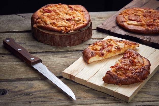 Пицца на деревянном столе с ножом