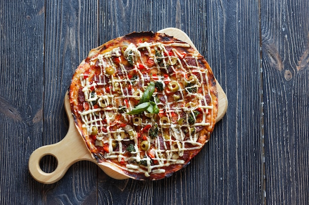 暗い木製のテーブルの上のピザ。上面図。