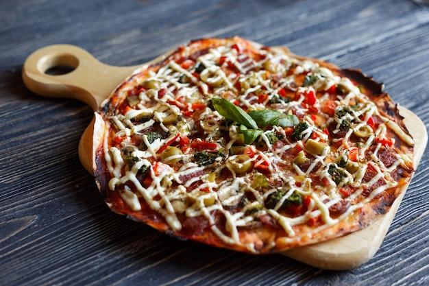 暗い木製のテーブルの上のピザ。