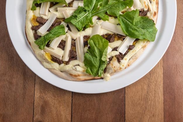 茶色の木製のテーブルでピザ