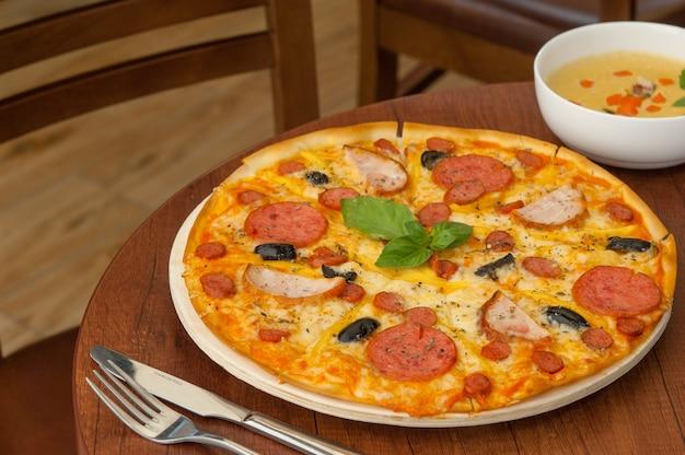 フォークとスープと台所のテーブルの上のピザ