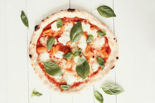 白い木製のテーブルでピザ