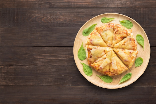 木製の背景のピザ。テキスト用のスペースをコピー