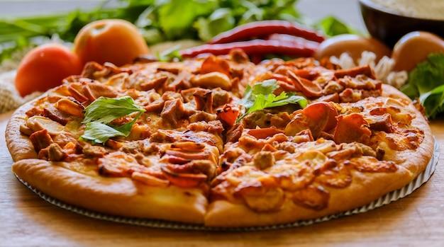 Пицца на деревянных фоне, вид сверху. пицца с фаршем, сельдереем и сыром моцарелла заделывают.