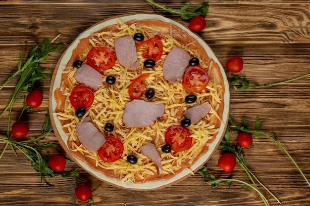 木の板にトマトとバジルのピザ、古い木製のテーブル、トップビューでイタリアンスタイル。