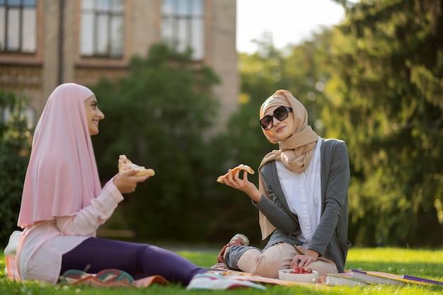 밖에서 피자. 잔디에 앉아있는 동안 외부 친구와 함께 피자를 먹는 선글라스에 이슬람 여성