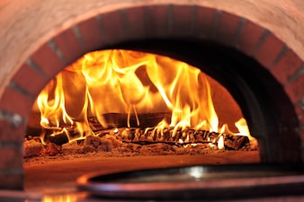 Pizza oven with fire in restaurant