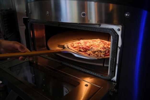 Печь для пиццы с открытой дверцей во время загрузки пиццы