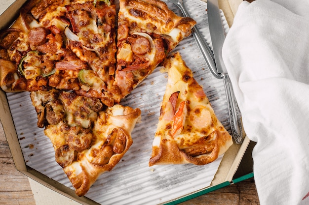 Pizza in the paper box on wooden table