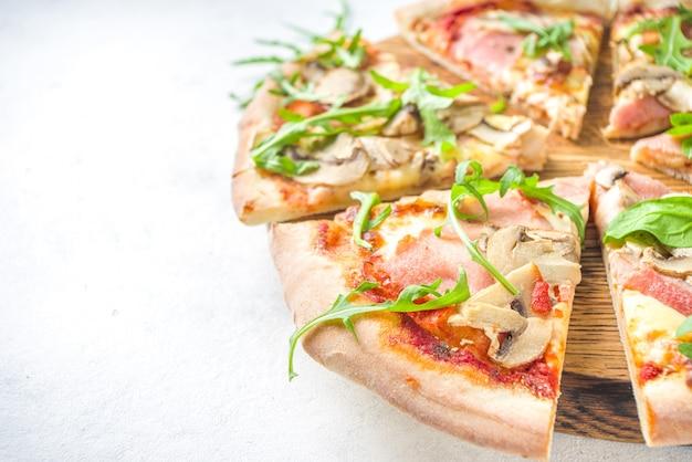 ピザパーティーのコンセプト。さまざまなフィリングのピザのセット、さまざまなピザのピース、ガラス、ワインのボトル。
