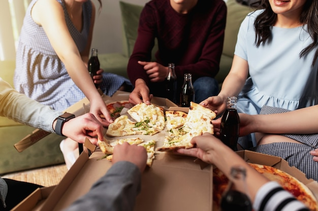Группа друзей на вечеринке с пиццей разговаривает, ест пиццу и пьет сладкую газированную воду