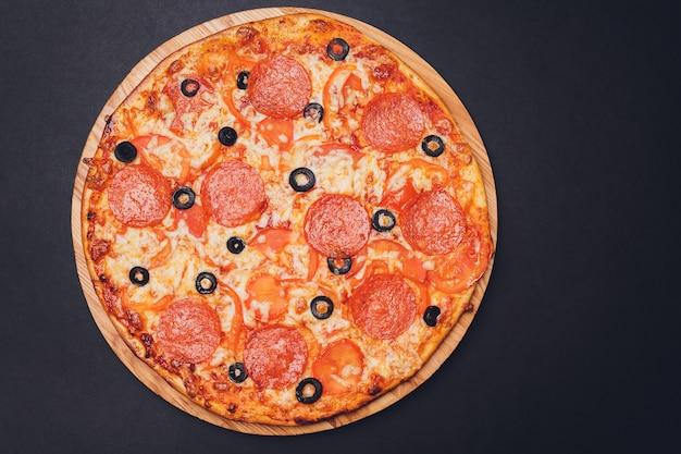 黒の背景にピザペパロニ、モッツァレラチーズ、オレガノ。