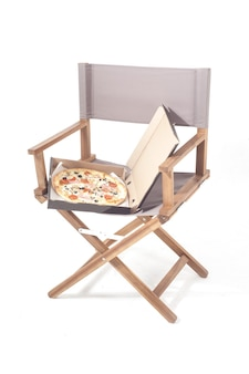 Pizza in pizza box on director chair isolated on white background