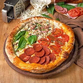 피자 콰트로 스타지오니 사계절 아티초크 버섯 토마토 햄 프로슈토 파마산 치즈와 바질로 만든 이탈리아 전통 식사.