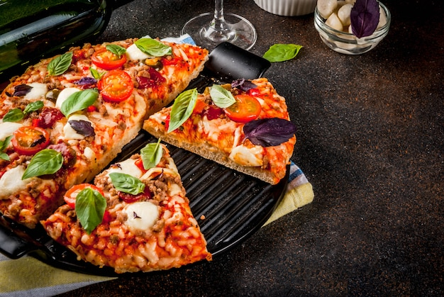 Pizza and red wine on dark background
