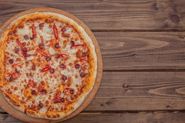 ピザレストランメニュー-ソーセージと唐辛子を使ったおいしいスパイシーなピザ。素朴な木製のテーブルで食材を使ったピザ