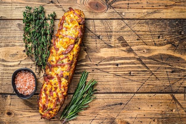 木製のテーブルにハム、ベーコン、野菜、チーズとバゲットパンのピザサンドイッチ。木製の背景。上面図。スペースをコピーします。