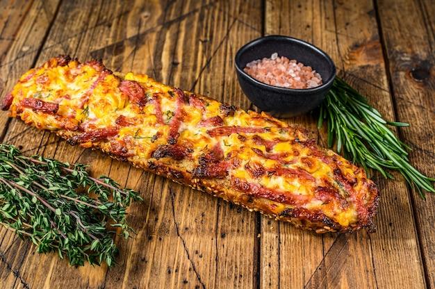 나무 테이블에 햄, 베이컨, 야채, 치즈를 곁들인 바게트 빵에 피자 샌드위치. 나무 배경입니다. 평면도.