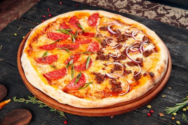 Пицца колбасная с мясом и луком на деревянном столе