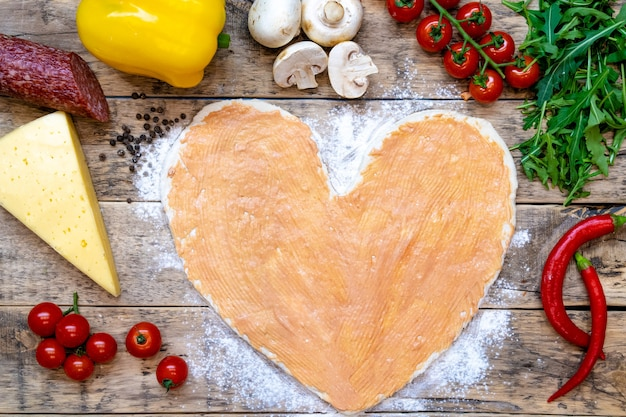 Pizza in the shape of a heart and ingredients for valentine's day, cooking process
