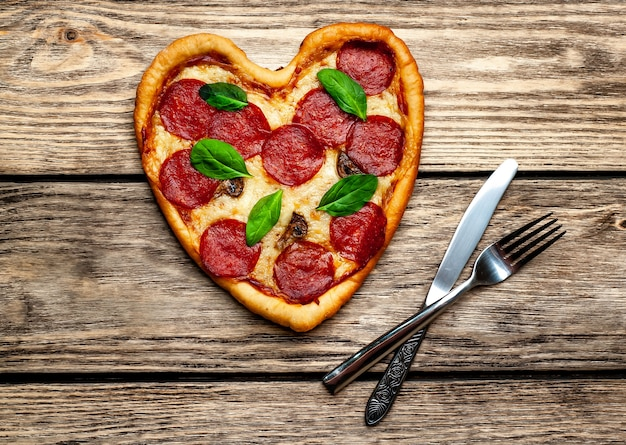 Pizza in the shape of a heart on a wooden table