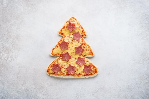 페퍼로니로 만든 별이있는 크리스마스 트리 모양의 피자