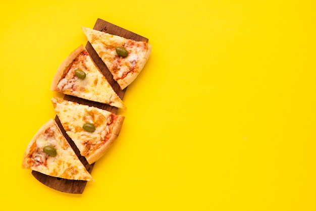Pizza slice arranged on wooden plate over yellow background