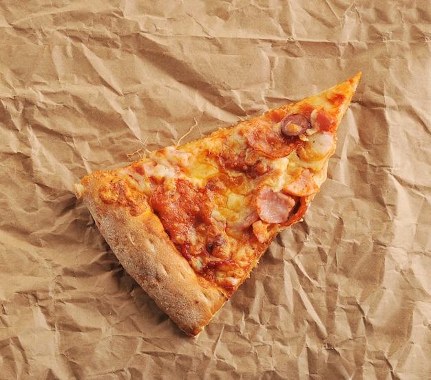 Кусочек пиццы с сыром и острой колбасой на бумаге