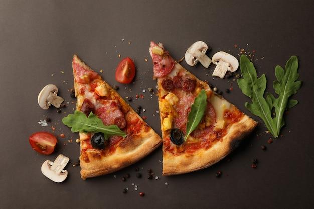 Ломтики пиццы и ингредиенты на темном