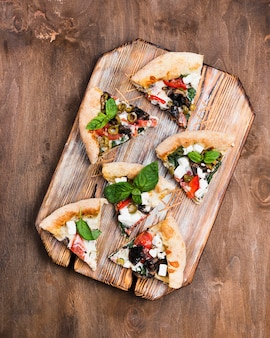 Pizza slices on cutting board above view
