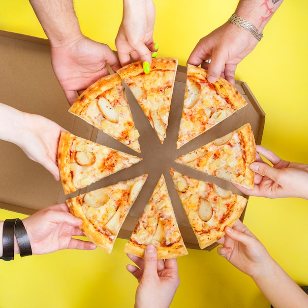 Pizza slices in the hands of a group of people top view on a yellow space. concept photo for pizzerias.