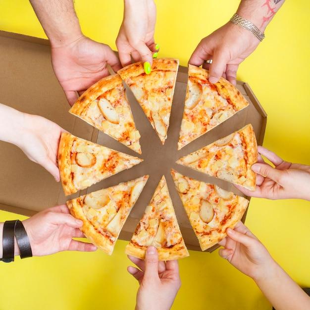 人々のグループの手でピザのスライスは、黄色のスペースの平面図です。ピッツェリアのコンセプト写真。
