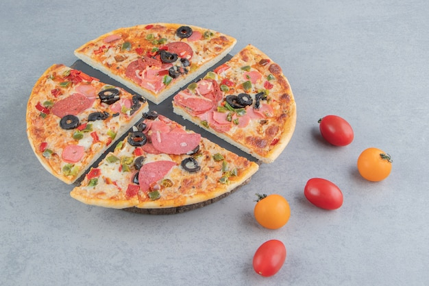 Fette di pizza su un vassoio accanto a pomodorini su marmo
