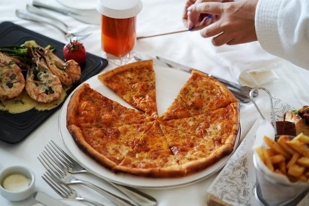 ピザのスライス、エビのソースとフライドポテトの白いテーブルのクローズアップ