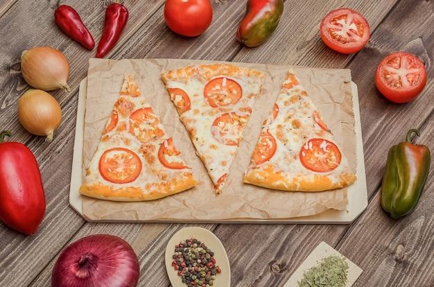 木製の背景に材料とボード上のチーズとトマトのピザスライス。