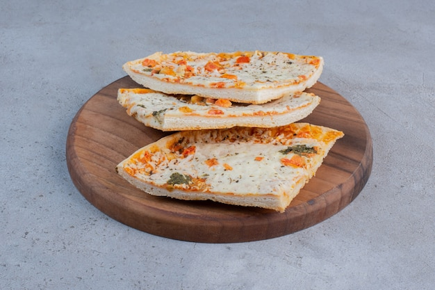 Fette di pizza su una tavola di legno su sfondo marmo.