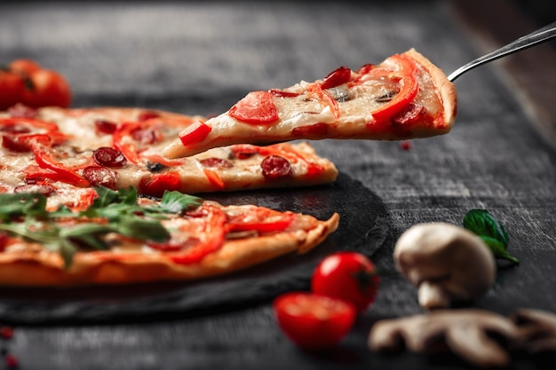 Pizza on a spatula with smoked sausages, cheese, mushrooms, cherry tomatoes, bell peppers