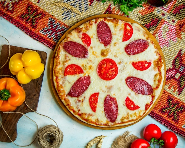 Pizza topped with sausages and tomato
