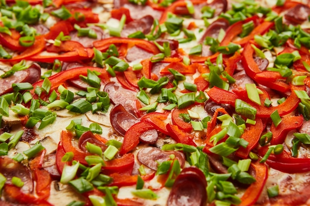 Пицца с большим количеством начинок: охотничьи колбаски, лук, сыр и болгарский перец.