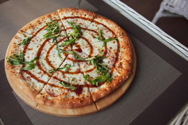 여름 테라스에서 회색 배경에 나무 접시에 arugula와 피자.