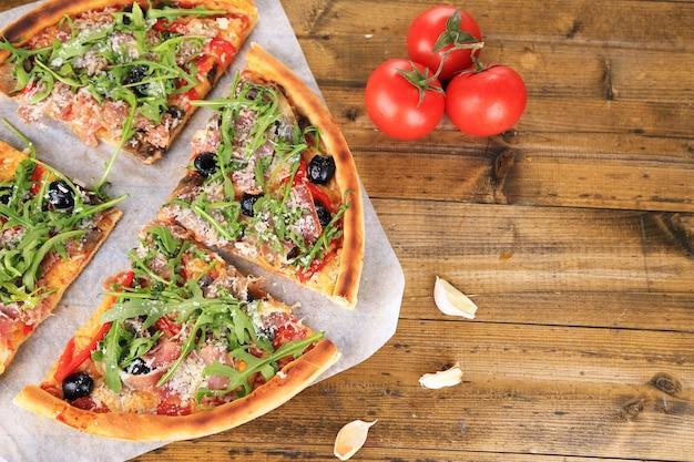 色の木の表面にルッコラのピザ