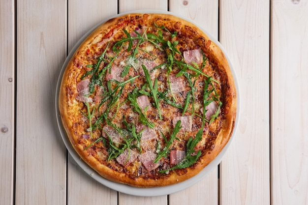Pizza with bacon, bell pepper, onion and arugula