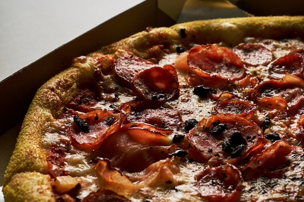 Pizza with bacon in a cardboard box on a dark background.
