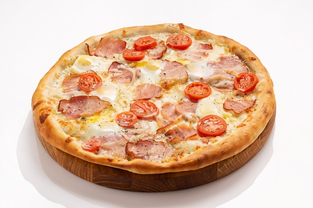 Pizza with bacon, cheese, egg and tomatoes isolated on white surface.