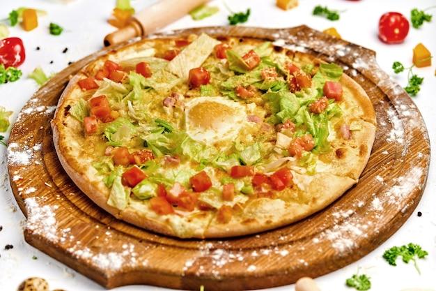 木の板にベーコン肉、卵黄、グリーンサラダを添えたピザ