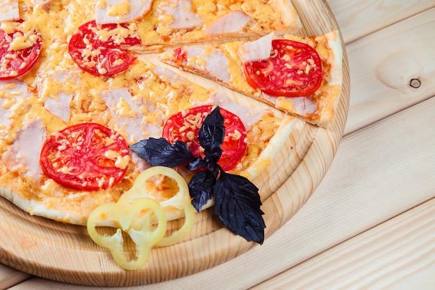 木製のテーブルにベーコンのピザ