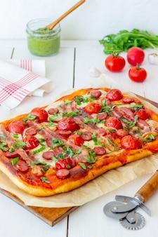 Пицца с беконом, колбасой, моцареллой, помидорами и базиликом. итальянская кухня. рецепт блюда.