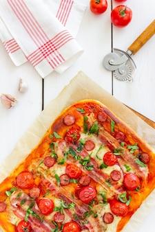 ベーコン、ソーセージ、モッツァレラチーズ、トマト、バジルのピザ。イタリア料理。レシピ。